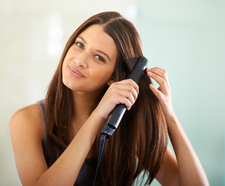 A woman using a hair straightener